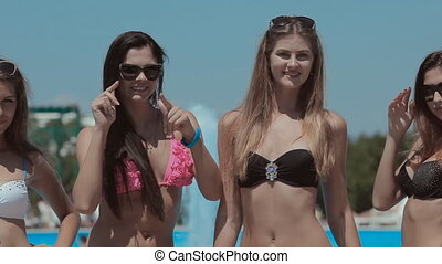 Cute girls with a beautiful figures standing near the pool