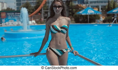 Beautiful young girl in a bikini walking near the pool at...