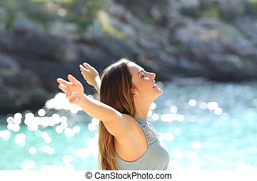 Happy woman breathing fresh air raising arms on holidays...
