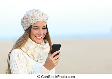 Woman in winter using a smart phone - Woman warmly clothed...