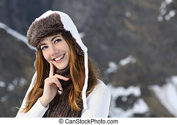 Woman warmly clothed thinking in winter and looking at side