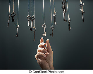 The Right Key - Hand choosing a hanging key amongst other...