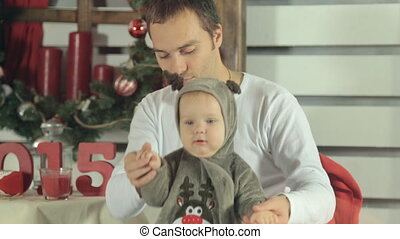 Dad plays with laughing baby dressed as a deer