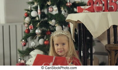 Carefree little blonde girl with long hair sitting near a beautifully decorated Christmas tree with a big box packed in red paper with a gift