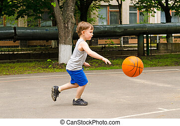 Little boy playing basketball running along the court in his...