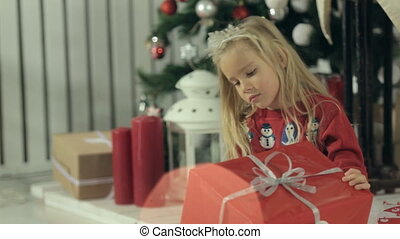 Amazing little girl sitting with her gift near Christmas tree