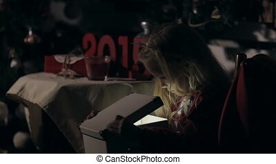 Little girl in the darkness opens the box curiously with the light inside on the new year