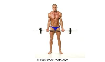Shirtless bodybuilder lifting heavy barbell weight at the...