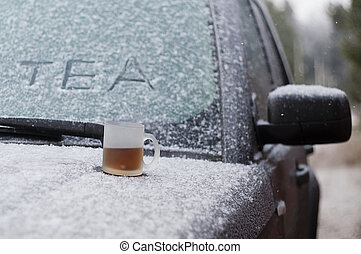 Cold Start - Cup of hot tea on a snowy car hood, concept of...