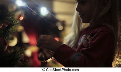 Mum with a small daughter decorate Christmas tree in the dark