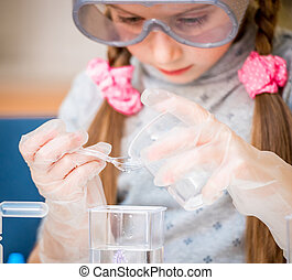 girl with flasks for chemistry - happy little girl with...