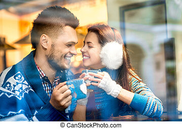 Young couple with coffee at the cafe in winter - Young...