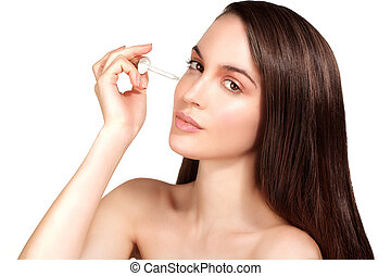 Beautiful model applying a cosmetic skin serum treatment on...