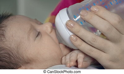 Maternal Care - Close up of little boy given to drink from...