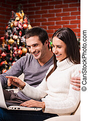 Buying online. Beautiful young couple using computer...