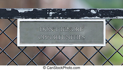 Dont ignore opportunities - Sign hanging on an old metallic...