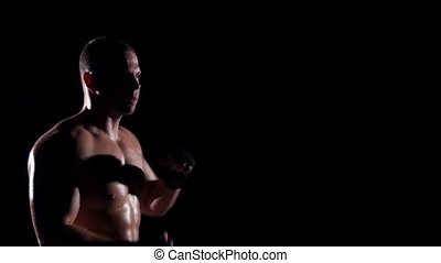 Boxer training shadow boxing over black background Slow...