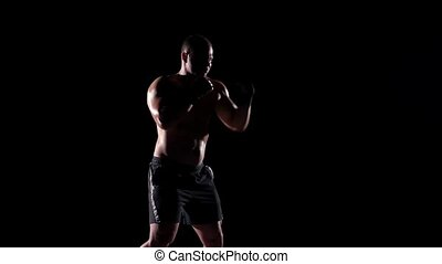 Boxer training shadow boxing over black background. Slow...