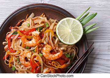 Asian rice noodles with shrimp and vegetables top view -...