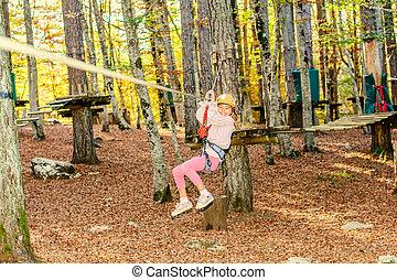 Zip line fun - Little girl is going on the zip line in...