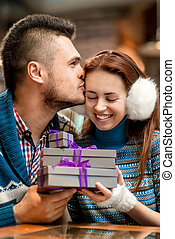 Young couple with gift boxes at the cafe in winter - Young...