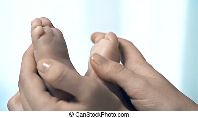 Tiny Feet - Close up of infant feet massaged by...