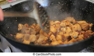Preparing paella Spanish tradition - Frying chicken to make...