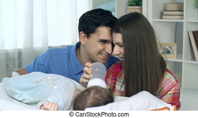 Fostering Child - Young parents feeding newborn child from...