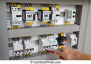 Technician working at electrical cabinet (using a...