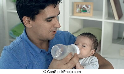 Proud Father - Close up of young father feeding his newborn...