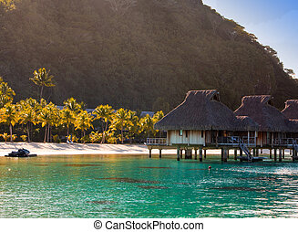 Morning on the tropical island. The sun ascends behind the mountain over a reed roof of a hut at the ocean