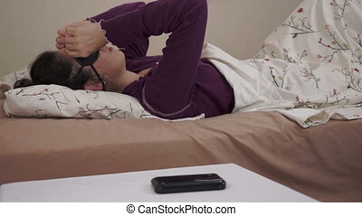 Woman Waking Cellular Phone Alarm - Woman wakes up in her...