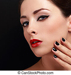 Makeup woman with red lips and black nails polish looking...