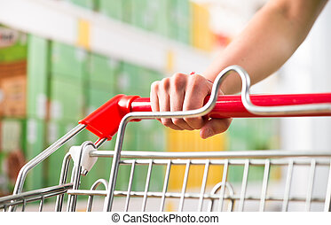 Supping cart and supermarket shelf - Female hand on shopping...