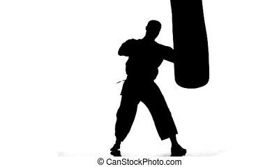 Silhouette karate man practicing on the sandbag on white background