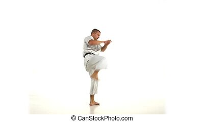Karate Man in a kimono hits foot on the white background