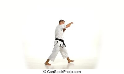 Karate. Man in a kimono hits foot on the white background. Slow motion.