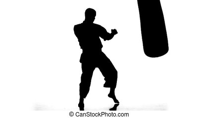 Silhouette karate man practicing on the sandbag on white...