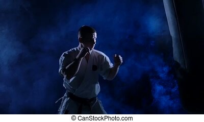 Silhouette karate man practicing on the sandbag on blue background. Slow motion