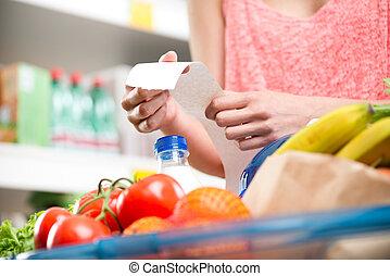 Supermarket receipt - Unrecognizable woman checking a long...