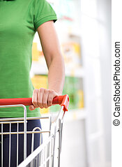 Woman with shopping cart - Young woman with trolley at store...