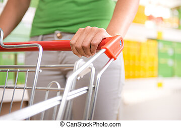 Woman with trolley at supermarket - Woman in green t-shirt...