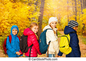 Back view of happy children wearing rucksacks - Back view of...