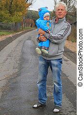 grandfather and his grandchild in rural landscape, autumn,...