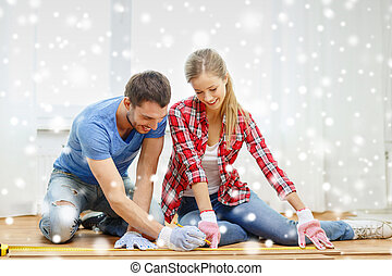 smiling couple measuring wood flooring - repair, building,...