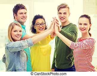 five smiling students giving high five at school - education...