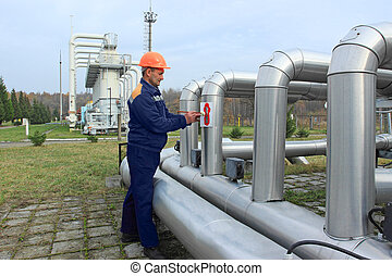 Worker draws arrows on pipes gas compressor station using...