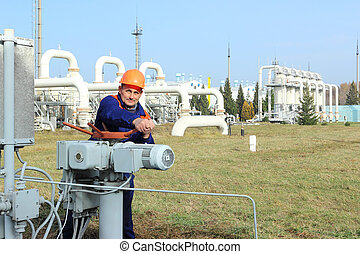 Worker opening bypass valve on gas compressor station