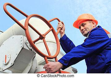 Worker turns big gas valve