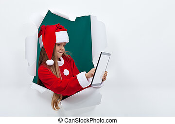 Little santa girl using tablet computer - with copy space -...